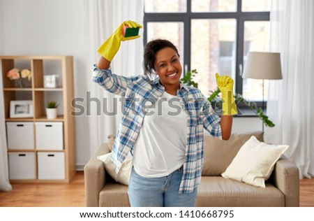 cleaning, housework and housekeeping concept - happy african american woman in rubber gloves with sponge at home #1410668795