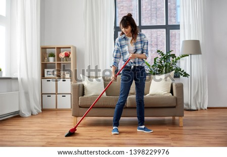 cleaning housework and housekeeping concept - happy asian woman with broom sweeping floor and dancing at home #1398229976