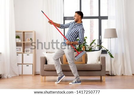cleaning, housework and housekeeping concept - indian man with broom sweeping floor and having fun at home #1417250777