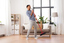 cleaning, housework and housekeeping concept - indian man with broom sweeping floor and singing at home