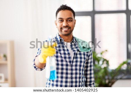 cleaning, housework and housekeeping concept - smiling indian man with detergent and rag on shoulder at home #1405402925