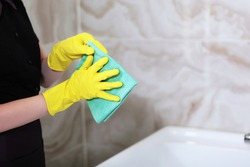 Cleaning in the bathroom. Marble tiles on the walls. Unrecognizable photo. Only hand. Copy space.
