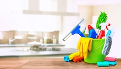 Cleaning items in a bucket on a wooden table infront of a kitchen background. Cleaning service concept with copy space