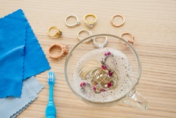 cleaning jewelry diamond ring with glass of hot water and dishwashing liquid on wood table background