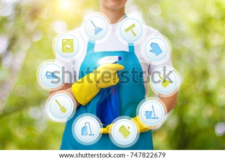 Cleaning lady provides cleaning services on blurred background.
