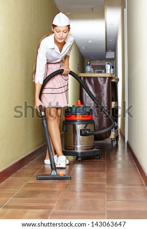 Cleaning lady with vacuum cleaner in hotel corridor