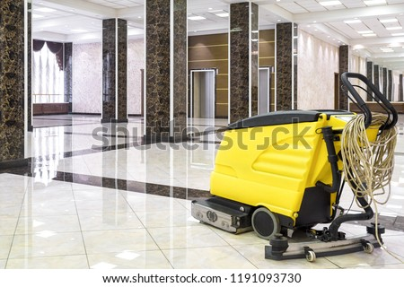 Cleaning machine in empty office lobby, yellow vacuum equipment is on clean shiny marble floor in commercial building. Concept of professional cleaning, maintenance and care service.