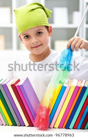 Cleaning my room - young boy with brush dusting books - stock photo