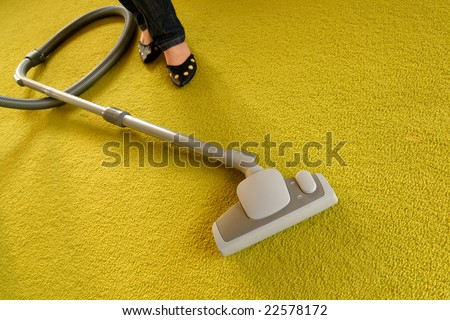 Cleaning of a green carpet with a vacuum cleaner