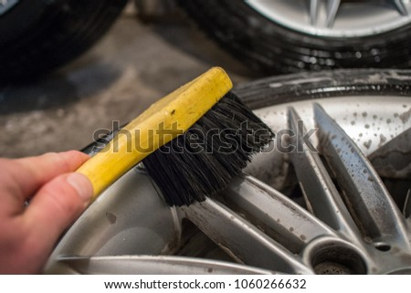 Cleaning of alloy or aluminium light wheels of a car with a yellow brush. Cleaning stubborn brake residue braking dust with cleaning solvent and a brush.