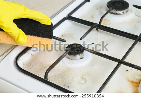 cleaning of dirty gas stove burners in kitchen room