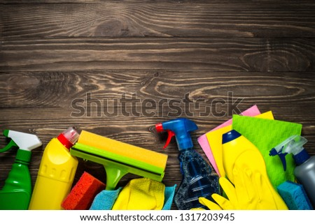 Cleaning product, household, sanitary supplies on wooden table. Top view with copy space.