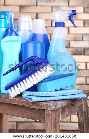 Cleaning products on shelf on bricks wall background