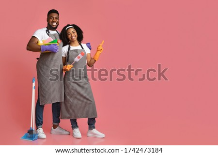 Cleaning Service Ad. Black Couple Of Professional Cleaners With Household Supplies In Hands Pointing At Copy Space On Pink Background Foto d'archivio ©