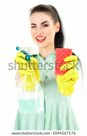 Stock Photo Cleaning service and work concept. Housewife with cheerful face and cleaning supplies. Happy girl wearing household gloves shows cleaning tools. Woman winks and holds sponge and household spray.