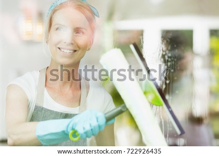 Cleaning service concept, happy middle-aged female cleaner washing window with a squeegee wearing protective gloves, photo behind glass #722926435