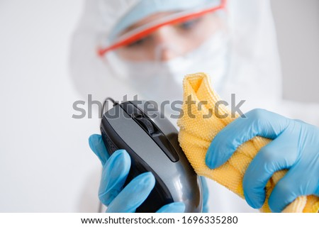 Cleaning service disinfects office Technics from coronavirus and germs, antiseptic processing computer.