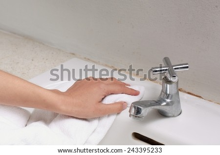 Cleaning Sink , female hand drying off kitchen sink with  towel