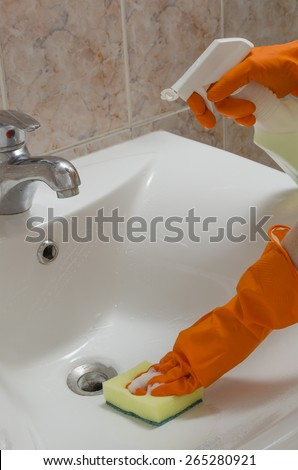 cleaning sinks in the orange gloves