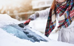 Cleaning snow from windshield, Scraping frozen ice, Winter car front windows clean.