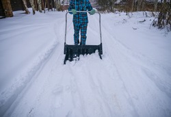 cleaning snow with a shovel. A woman with a big shovel removes snow from the road after a blizzard