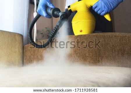 cleaning  sofa with steam generator, hands in blue glove hold steam genetator and hose with brush, which produces steam for disinfection from microbes, dirt, allergy and viruses, home cleaning concept