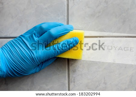 Cleaning sponge held in hand while cleaning bathroom with french lettering nettoyage (cleaning in english translation)