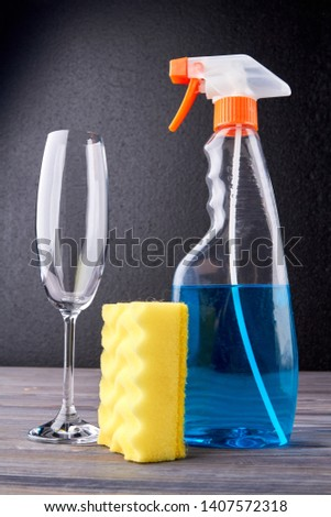 Cleaning spray, wine glass and kitchen sponge. House cleaning supplies. Household chores concept. #1407572318