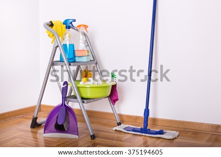 Cleaning supplies on ladder and mop and brush with dustpan on the parquet in the corner of room