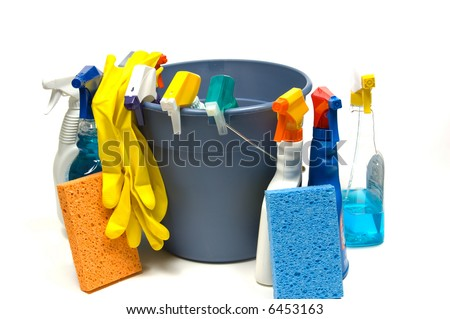 Cleaning supplies on white background including several spray bottles of chemicals, a bucket, gloves and sponges