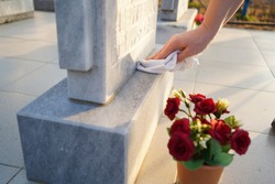 Cleaning the cemetery. A woman's hand washes the grey monument at the grave with a rag. Parents Saturday in Russia. business beautification of the graves.