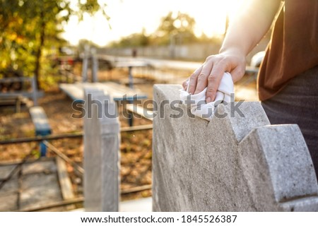 Cleaning the cemetery. A woman's hand washes the grey monument at the grave with a rag. Parents Saturday in Russia. business beautification of the graves. Foto stock ©