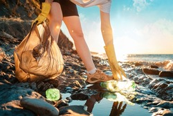 Cleaning the coastal zone. An activist picks up a plastic bottle on the beach. Close up of hands. In the background, the sea and the sunset. Bottom view.
