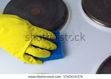 cleaning the electric stove with cleaning products in the kitchen at home. Household, household chores. Clean house, clean #1562616376