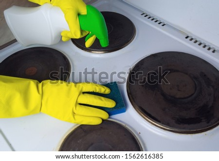 cleaning the electric stove with cleaning products in the kitchen at home. Household, household chores. Clean house, clean #1562616385