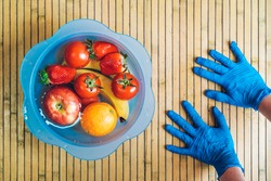 Cleaning the fruit with water and lye to eliminate the spread of the coronavirus. Hands with blue latex gloves and a blue bowl with different fresh and clean fruits on a wooden base.