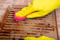 Cleaning the grill. Hands in yellow gloves clean the dirty grill of grease and burns with a cleaning agent. electric grill hygiene, cleaning contaminants with grill grates