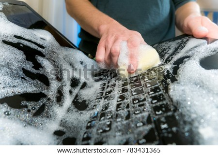 Cleaning the hard drive concept. Washing the laptop with dish soap.Also a symbol for making a big mistake!