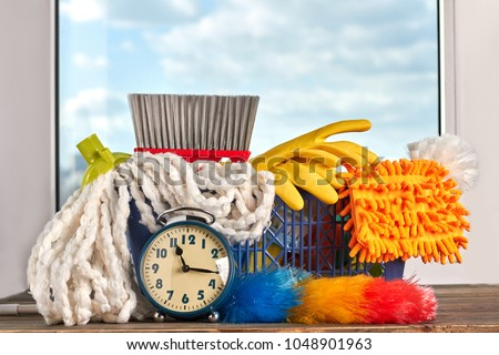 Cleaning time with cleaning supplies. House cleaning products and blue vintage alarm clock. Time for spring cleaning. #1048901963