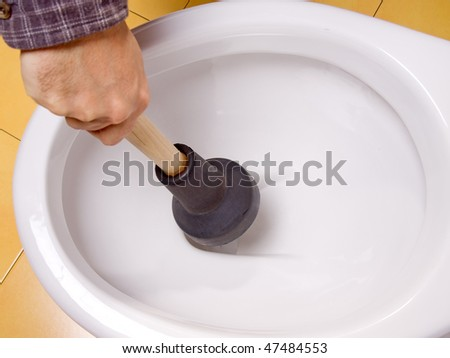 Cleaning toilet bowl with lavatorial bell. Man's hand cleans clogged toilet. Clean blocked drain the toilet bowl. Maintain cleanliness of drains in the bathroom. Service of plumbers.