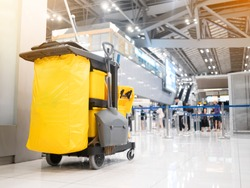 Cleaning tools cart cleaner in the airport. Bucket and set of cleaning equipment in the terminal airport. Concept of service clean.