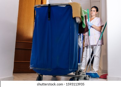 Stock photo of a Cleaning trolley and a hotel cleaner next door with a broom in hand. Lifestyle