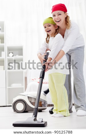 Cleaning up the room together - woman and little girl with vacuum cleaner