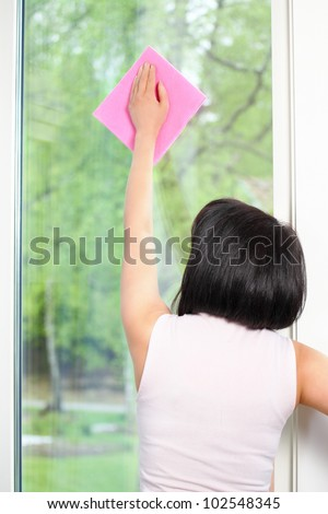 Cleaning window rear view of housekeeping woman