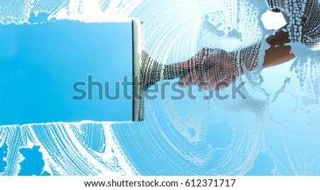 cleaning window with squeegee blue sky