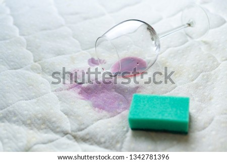 Cleaning wine stain with sponge. Spilled wine on white bed sheet. Dropped wineglass. Unlucky, unfortunate situation. #1342781396