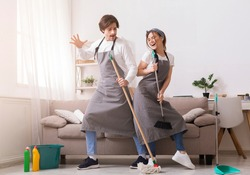 Cleaning With Pleasure. Cheerful Couple Having Fun While Tidying Home, Dancing With Mop And Broom, Free Space