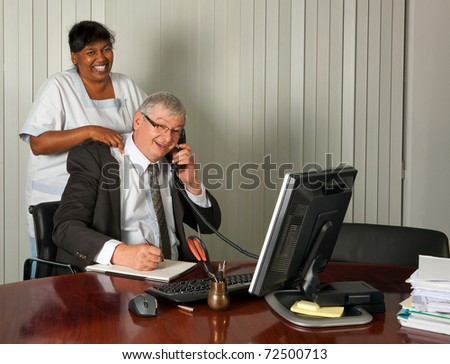 Cleaning woman giving the manager of the office a neck massage