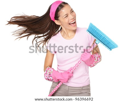 Cleaning woman singing having fun during spring cleaning. Funny woman cleaning wearing pink rubber gloves singing into broom. Mixed race Caucasian / Asian female model isolated on white background.