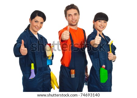 Cleaning workers in a row holding cleaning products and giving thumbs up isolated on white background